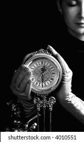 Monochrome picture of a beautiful girl with a clock (focus on clock)