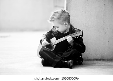 Monochrome portrait of defiant, rebellious child, boy in leather jacket  and iroquois haircut, playing rock music on the guitar. The concept of children's interest in music.