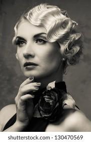 Monochrome portrait of elegant blond retro woman  in dress with beautiful rose flower