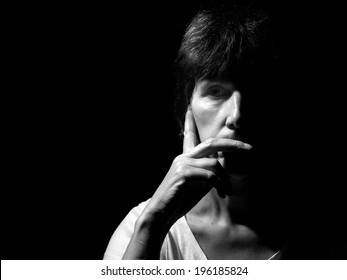 Monochrome portrait, face of a middle aged woman. Pensive, thoughtful. Rembrandt style lighting.