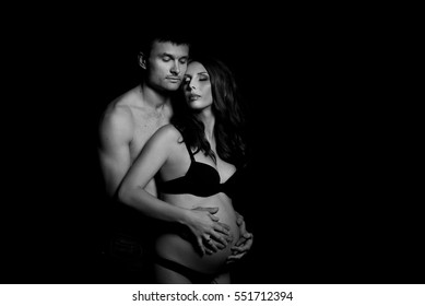 Monochrome portrait of happy loving couple in a moment of love and tenderness. Pregnant woman with hands over tummy. Black and white photo