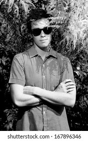 Monochrome portrait of hipster boy in sunglasses with crossed hands