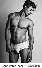 Monochrome portrait of a male model with perfect body in white underwear posing over grey background. Close-up. Studio shot.