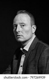 Monochrome portrait of man in business suit and retro thirties moonlight studio light.