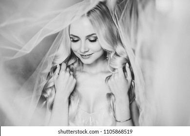 Monochrome portrait of sensuality and charming smiling young blondie. Beautiful sexy lady with long hair, and perfect make up dreaming with closed eyes. Concept of beauty. Morning of bride.