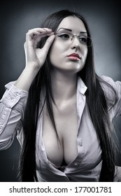 Monochrome portrait of a sexy teacher wearing glasses and displaying her cleavage