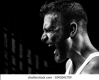 Monochrome portrait of a strong man with a beard, face in blood. He looks at the camera with different emotions. Blood and sweat dripping down his face.
