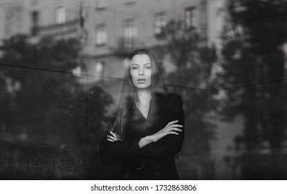 Monochrome portrait of a young fashionable woman wearing stylish coat. Female fashion, beauty.