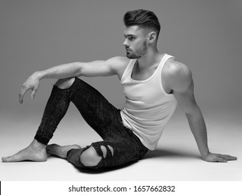 Monochrome portrait of a young man with a beard on a gray background. A muscular man in a t-shirt. Studio portrait. Fitness, fashion and beauty