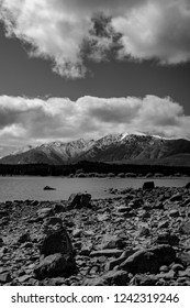 Monochrome rocky Ruataniwha Inlet foreshore at low tide with snow on top distant mountains under dramaitc clouds at Collingwood, Tasman Bay New Zealand.