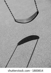 A monochrome shot of an empty swing at a playground with harsh lighting and distinct shadow.
