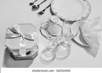 Monochrome still life , Table setting: black and white plates and cutlery set on white background.