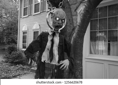 Monochrome Version of Decrepit Rotting Wrinkled Skin Corpse of an Old Ghoul whose Eyes are Glowing as He Hangs in a Suit and Tie with His Head in a Vice from a Tree in Front of Townhomes at Dusk