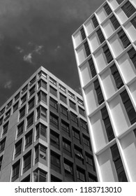 monochrome vertical view of a white high white concrete buildings cloudy sky