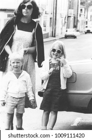 Monochrome vintage 1970s mother with daughter and son running errands.
