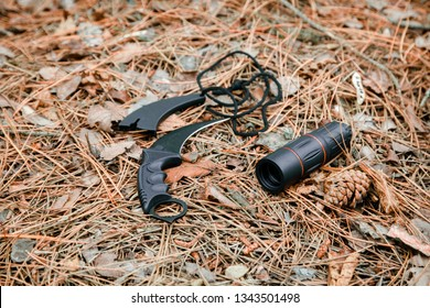 monocle and karambit knife on the ground covered with pine needles