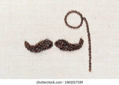 A monocle and a mustache all made with coffee beans on creamy linea canvas, shot from above, aligned in the center, closeup.