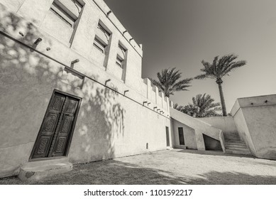 A monocrhome image of the courtyard of a restored traditional arabian house with carved wooden doors, palm trees and stairs leading to the roof.