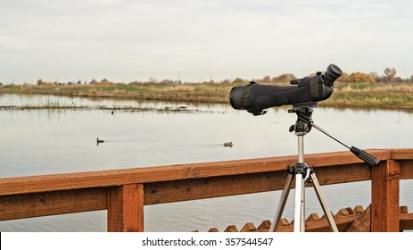 A monocular mounted on a tripod is ready for birdwatching on a bord-walk