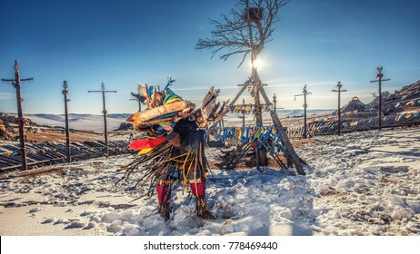 Monolia shaman doing authentic ritual of summoning spirits. shaman with jewelry holding drum with incense. Shamanic ritual in winter. Ethnic traditions.