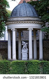 Monolith gazebo with white columns and two angels in the center, downtown Bruges, Belgium.
