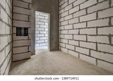 Monolithic brick basement wall. heating pipes lie on floor. New empty room. Сonstruction stage of residential monolithic house. Layout of building materials bricks. unfinished, incomplete, pending.