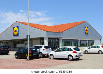 MONOPOLI, APULIA, ITALY - July 12, 2019. Cars are parked and people are shopping in modern building of Lidl supermarket chain. Lidl has many discount grocery stores in twenty European countries.