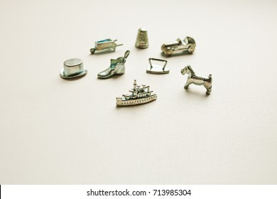 Monopoly board game, playing pieces on white background