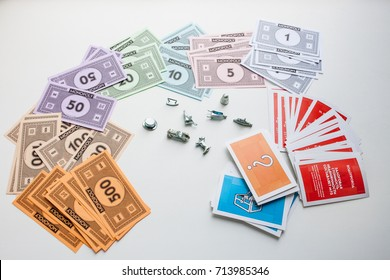 Monopoly board game, playing pieces and cards on white background