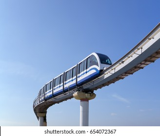 Monorail train moves on railway girder against background of blue sky