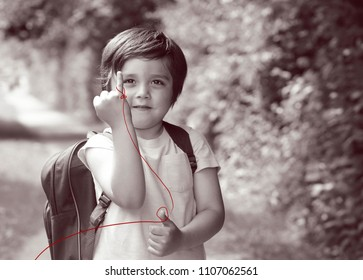 Monotone image with grain of Cute kid boy showing little finger with red thread,Portrait of adorable child showing pinky finger wrapped with red thred,Gesture of making a promise or Love sign concept