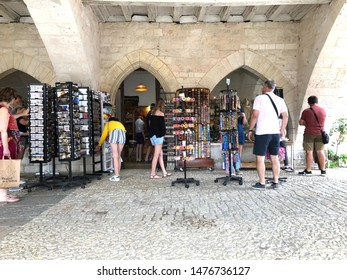 Monpazier, France; July 18 2019: tourists buying postcards and bracelets from a shop in the bastide town of Monpazier in France