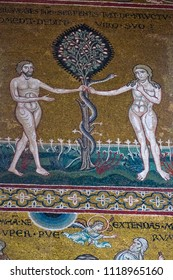 Monreale, Palermo, Sicily, Italia - April 4, 2018: a detail of the Byzantine mosaic of the duomo.Adam and Eve with the Tree of Knowledge of Good and Evil in the garden of Eden