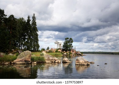 Monrepos Park (English landscape park). Vyborg. Russia. Leningrad Region. The Temple of Neptune, Antique Pavilion at the Stone Cape in Vyborg Bay with thunderclouds. Sunny summer nature photo