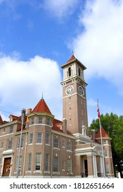 Monroe County Courthouse, in Clarendon, Arkansas, is a tan brick with red roof.  Clock tower is square.