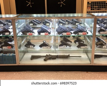 MONROE, LA, USA - AUGUST 15, 2017: Guns are sold publicly and legally in Monroe. There are different types & sizes of guns, such as rifles, pistols, being displayed in a glass counter of a shop.