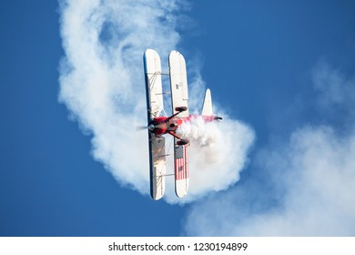 MONROE, NC (USA) - November 10, 2018:  An aerobatic biplane performs a corkscrew manuver in deep blue sky at the Warbirds Over Monroe Air Show.