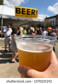 Monroe Wisconsin USA, September 2018 Cheese Days Festival. Close up of a hand holding a clear plastic cup of beer in front of a blurred background of the beer tent and festival goers.