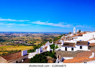 Monsaraz castle rocky medieval interior walls. Typical quaint whitewash buildings and red clay tiles rooftops. Yellow plains from Alentejo region, Southern Portugal. June, 2016.