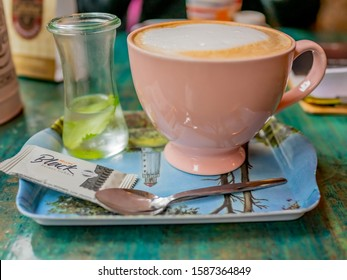 Monschau, Eifel, Germany – December 08 2019.Close up and selective focus of a cup of milky coffee on a tray with a complimentary biscuit, teaspoon and a glass of mint water
