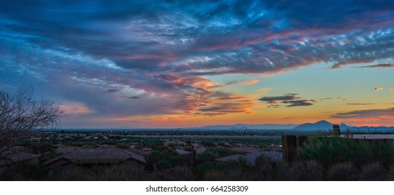 Monsoon Sunset - A big sky sunset awash in pink and peach is framed by a foreground of residential structures.  The large cloud formations is typical during monsoon season in Scottsdale, AZ.
