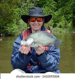 A monster black crappie fish being held horizontally by a smiling women angler in a hat and sunglasses on a brown water bay in spring time on a sunny day
