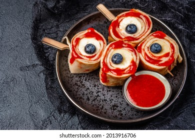 Monster Bloody Eyeballs for Halloween. Crepes roll up with banana and strawberry jam