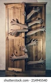 Monster with a lot of hands trying to escape from old grungy cupboard, Halloween theme