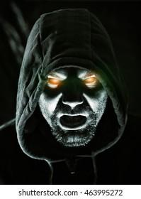 Monster in hood with glowing eyes