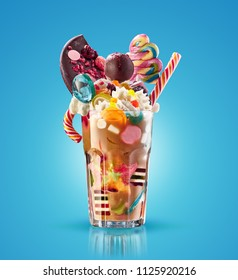 Monster shake, freak caramel shake isolated. Colourful, festive milk shake cocktail with sweets, jelly. Colored caramel milkshake array of different childs sweets and treats in glass on white