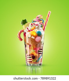 Monster shake, freak caramel shake isolated. Colourful, festive milk shake cocktail with sweets, jelly. Colored caramel milkshake array of different childs sweets and treats in glass on green