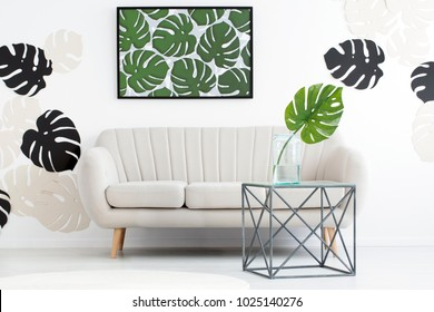 Monstera leaf in a vase on the table in front of a couch in living room interior with green poster on white wall