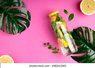 Monstera leaves and bottle tropical water on pink background. Detox fruit infused water, citrus fruits and mint leaves. Top view, flat lay, copy space