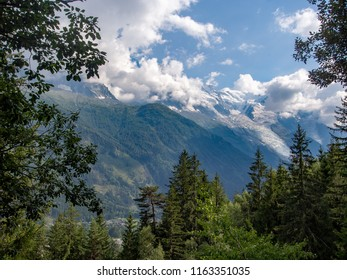 Mont blanc and the European Alps near Chamonix, Haute Savoie, France. Mountains seen through trees from the popular footpath 'petit balcon sud' ie small south trail.